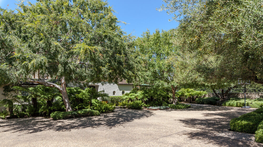 The yard has a spacious walkway showcasing the beautiful landscaping trees surrounding the area. Images courtesy of Toptenrealestatedeals.com.