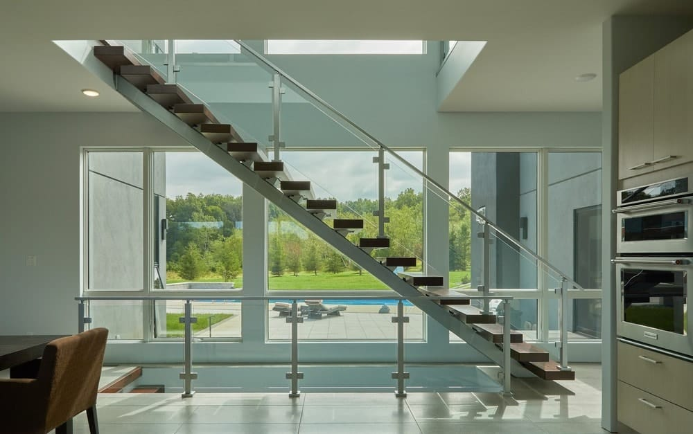 This is a view of the floating modern staircase with wooden steps and glass walls on its sides along with a large glass wall on the far side that brings in natural lighting.