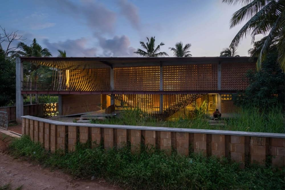 This is a street view of the house that has slatted outer walls that glow warmly form the interior lights. These are paired with the landscape of tall trees. thick shrubs and a red brick outer fence lined with shrubs on the outside.