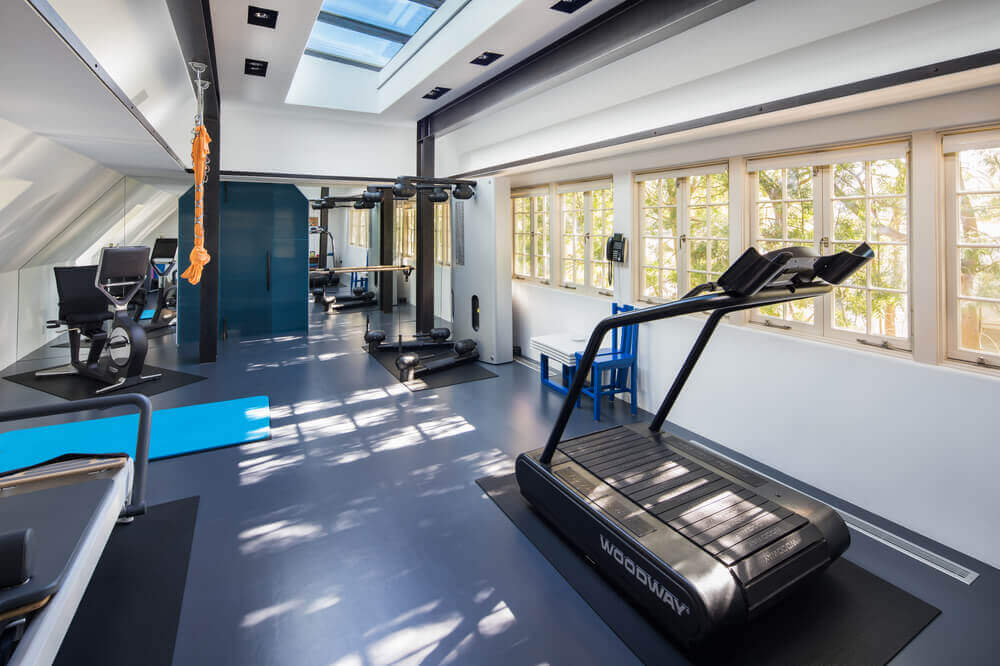 There's a home gym too featuring high-end workout equipment. The area has a custom ceiling and white walls. Images courtesy of Toptenrealestatedeals.com.