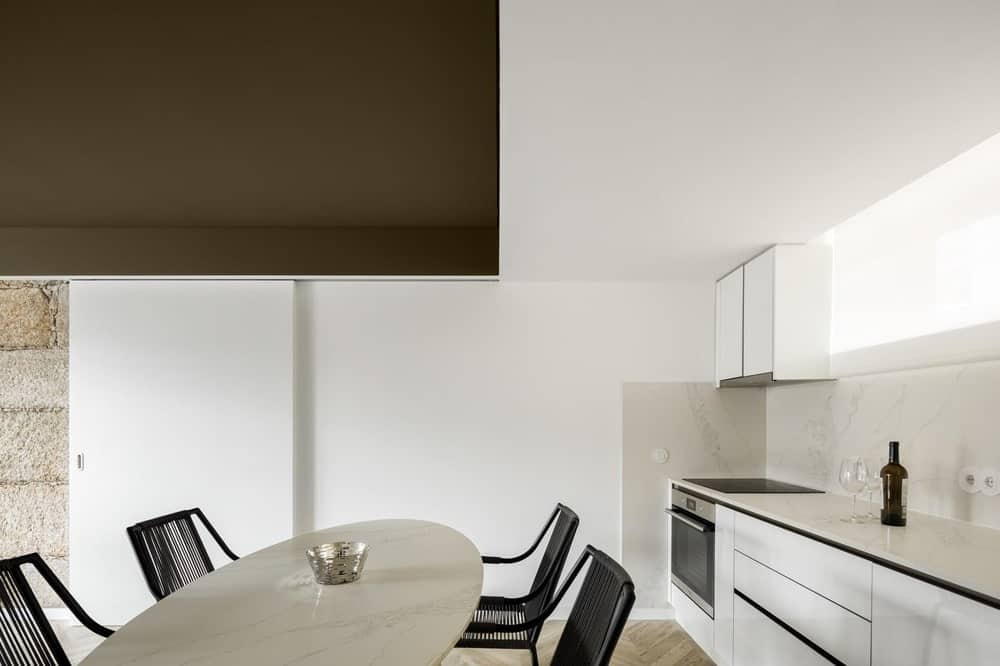 This is an eat-in kitchen that has white cabinetry against the wall topped with a dark green ceiling over the dining area of the kitchen that has outdoor furniture.