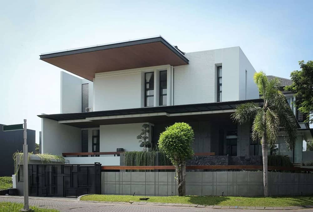 This is a view of the house exterior that has bright white exterior walls, a large roof panel above and gray concrete fence walls. These are complemented by the landscaping that has trees, creeping vines and grass lawn lining the outer wall.