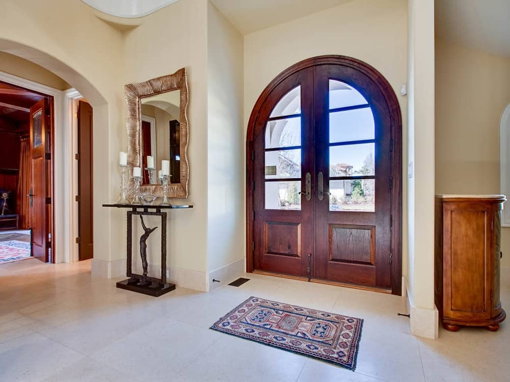 The beige walls of this charming foyer is complemented by the arched wooden main door filled with glass panels that bring in natural lighting. On the side is a simple console table topped with a wall-mounted mirror.