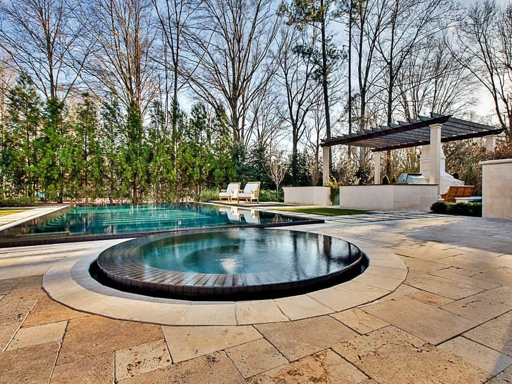 This is the gorgeous backyard of the house that features a beautiful pool with an attached zero-edge jacuzzi-type pool. On the side of the pool is a charming cabana fitted with trellises and an outdoor grilling station with a background of tall trees that provide shade and privacy.