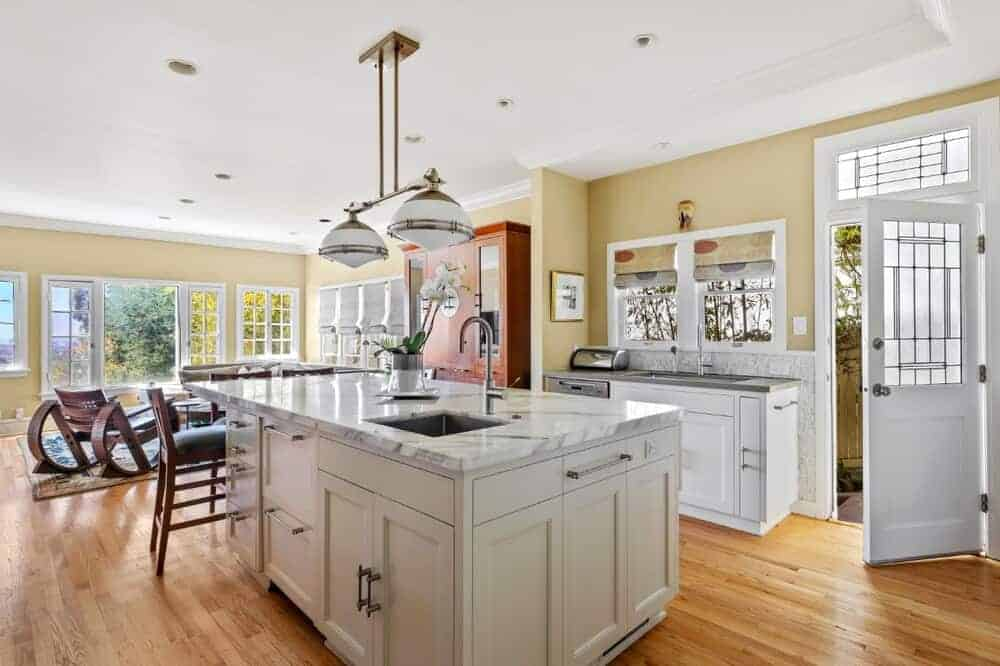 This is the kitchen with a large kitchen island that has a white marble counter to pair with the white cabinetry and the hardwood flooring. This is topped with large dual lighting.