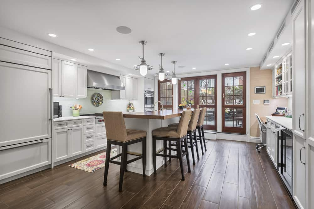 The large eat-in kitchen has a kitchen island in the middle with a butcher block counter topped with three pendant lights hanging from the white ceiling that matches the cabinetry.