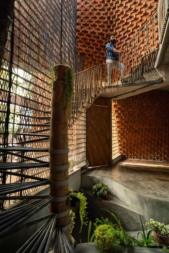 This is a close look at the foyer and staircase that are adorned by the landscaping of potted plants and creeping vines placed on strategic spots to enhance the aesthetic.
