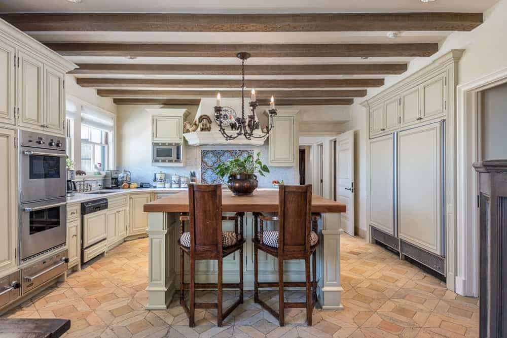 The large kitchen has a kitchen island in the middle of the terracotta-tiled flooring topped with a chandelier hanging from a beamed ceiling that matches the surrounding cabinetry contrasted by the stainless steel appliances.