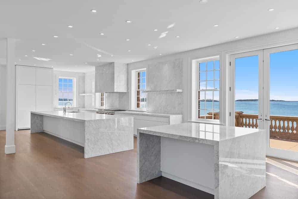 The large kitchen has large slabs of marble and has enough space for two kitchen waterfall islands that match the walls and ceiling brightened by the natural lighting.