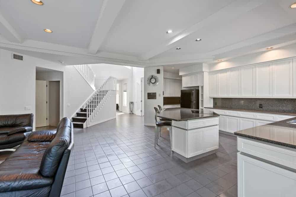 A few steps from the family room area is the kitchen that has a large kitchen island paired with stools for a breakfast nook paired with white cabinetry lining the walls contrasted by gray counter and backsplash.