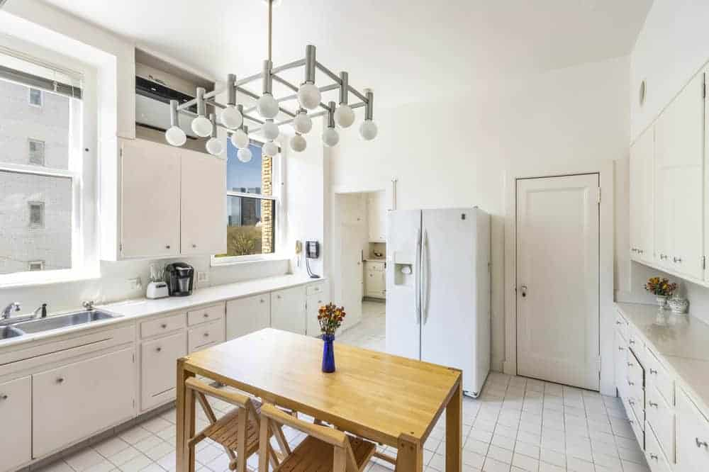 This is a view of the kitchen with its bright cabinetry lining the walls to match the bright floor tiles contrasted by the wooden table in the middle with two wooden chairs.