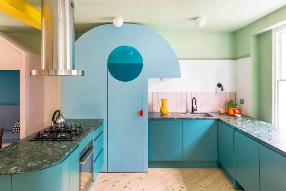 This is a look at the eclectic kitchen with blue-green cabinetry with a peninsula and pink subway tiles on the backsplash. The fridge also has the same tone as the cabinetry.