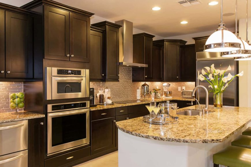 The L-shape layout of this elegant kitchen is paired with a beige countertop and backsplash that is augmented by the cabinet lighting. This goes quite well with the dark and classic cabinetry complemented by the stainless steel handles and appliances.