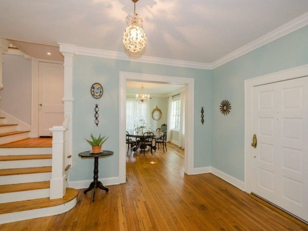 Entry of the house featuring hardwood flooring lighted by a charming pendant light.