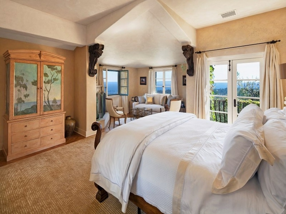 This charming bedroom has beige walls and a beige arched ceiling brightened by the glass windows and doors. There is also a lovely sitting area in an alcove at the corner.