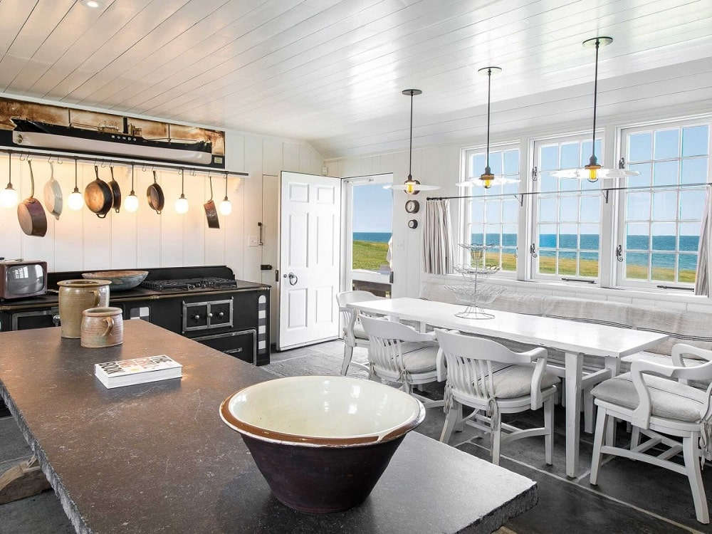 The kitchen has a large kitchen island and dark hardwood flooring that is contrasted by the wooden table and chairs of the informal dining area beside it.