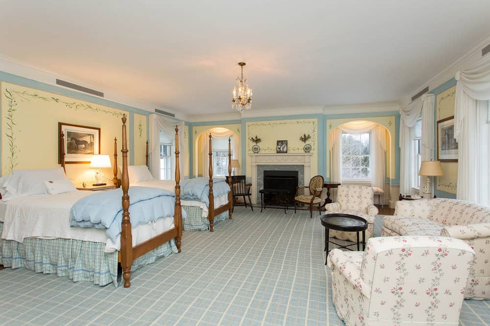 A large bedroom suite with elegant walls and carpeted flooring. The room offers two bed set and a personal living space, along with a fireplace.