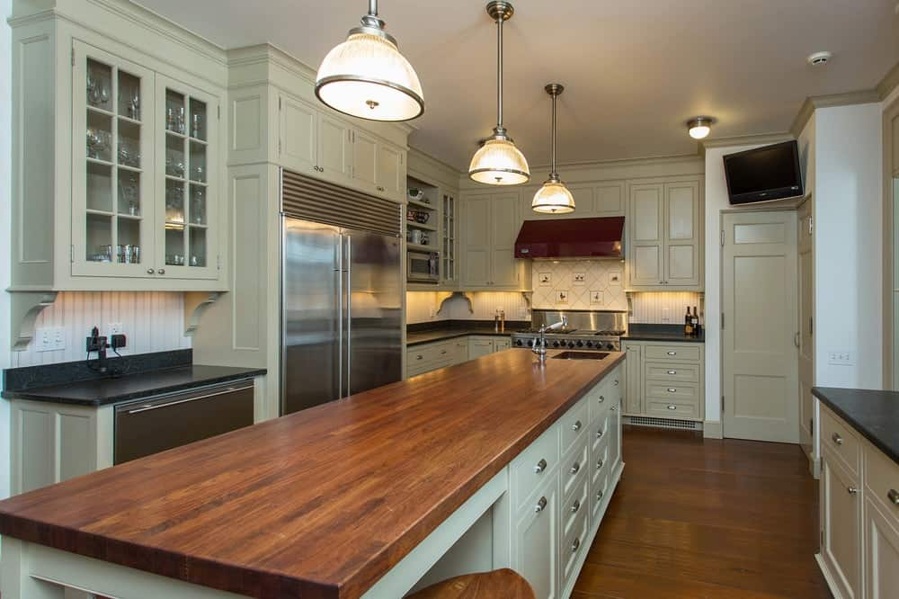 This kitchen offers a long center island featuring a thick plank countertop. It has space for a breakfast bar and is lighted by pendant lights.