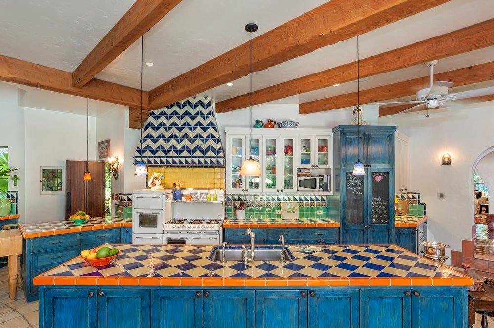 The kitchen has blue and white checkered patterns on its countertops that pair well with the vent hood and the blue cabinetry that contrasts the white walls and ceiling.