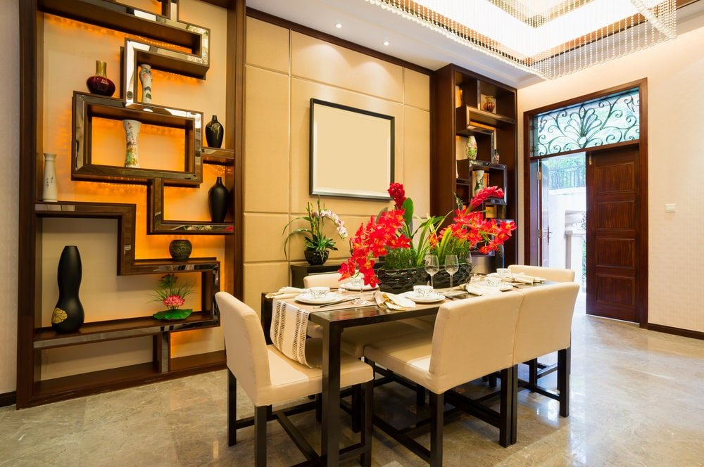 This dining room offers a sleek dining set and a black buffet table flanked by stylish shelvings that are filled with antique vases. It is illuminated by a large beaded chandelier that hung from the gorgeous tray ceiling.
