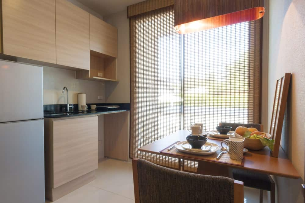 This is a simple and compact Asian-style dine-in kitchen that has bare wooden cabinetry on its light gray wall adjacent to the bright and tall window with a bamboo shade. This matches well with the pendant light hanging over the small dining table.