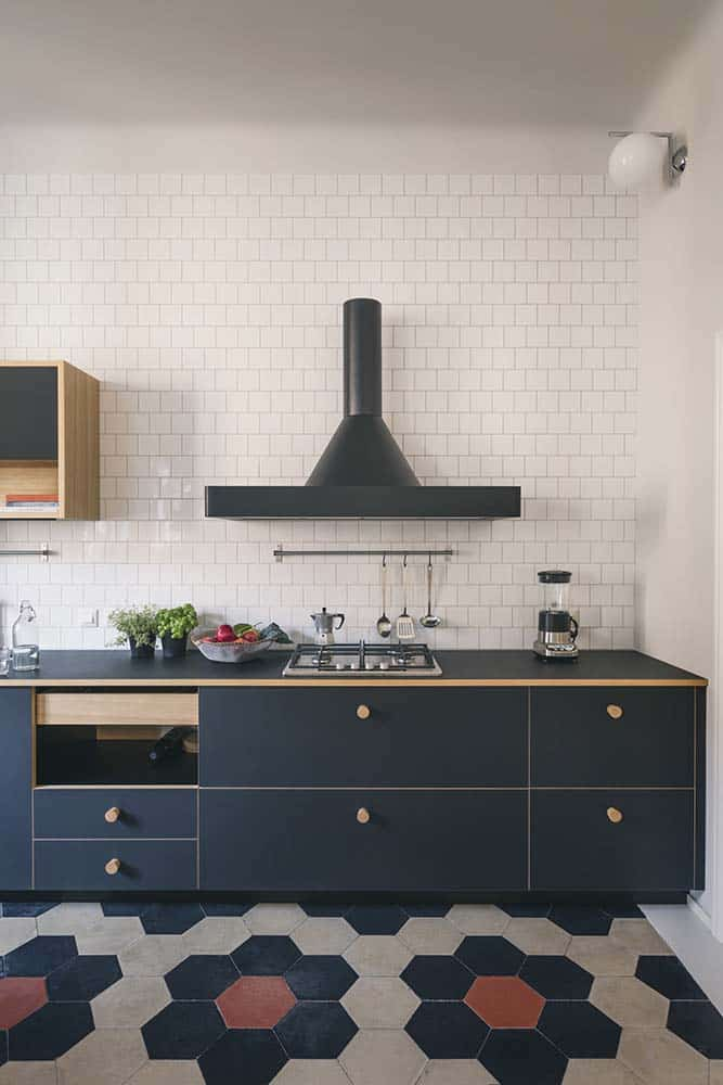This is a close look at the kitchen that has black cabinetry to contrast the white subway tiles of the backsplash. These are then complemented by the patterned colorful tiles of the floor.