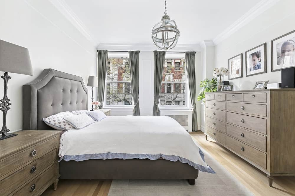 This bedroom has a bed that has a gray cushioned headboard making it stand out against the bright wall. The headboard matches well with the gray curtains of the tall windows as well as the gray area rug over the light hardwood flooring.