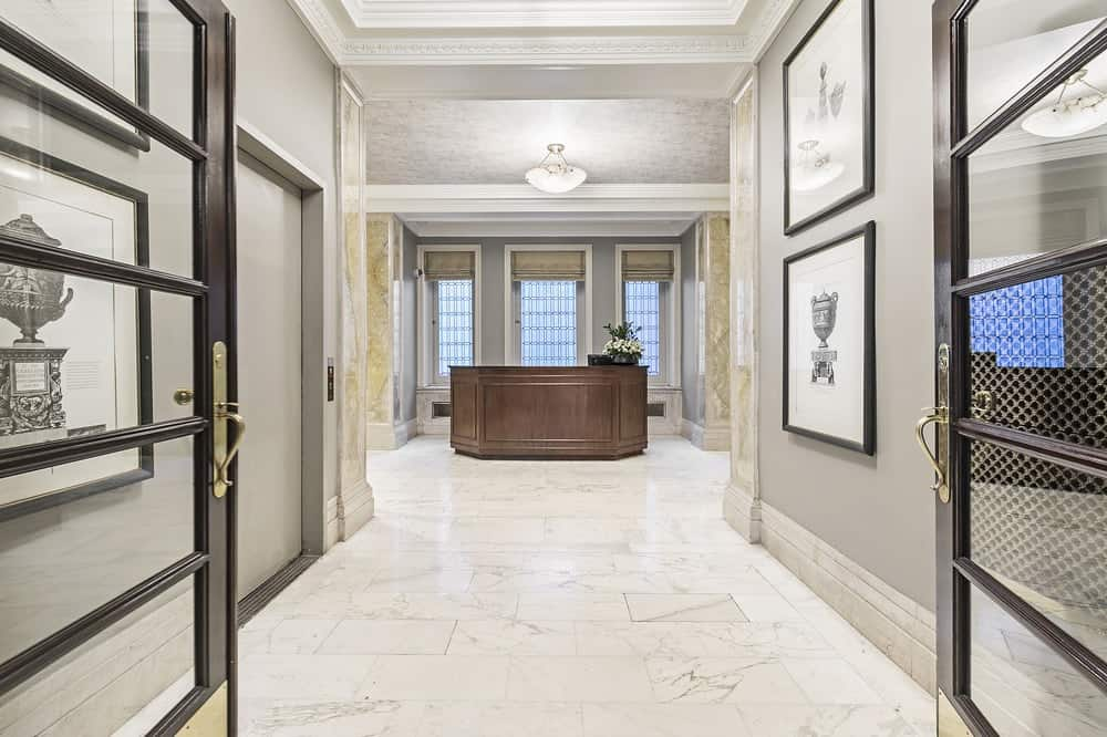 This is a elegant foyer and lobby with light gray walls, tall coffered ceiling and white marble flooring that makes the dark wooden counter stand out on the far side by the tall windows.