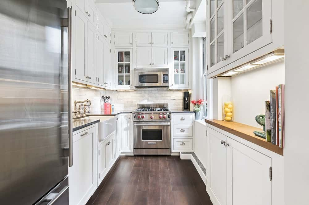 This is the galley-style kitchen of the apartment with a rich dark hardwood flooring to contrast the white shaker cabinets and drawers. On the far end is the stainless steel stove-top oven.