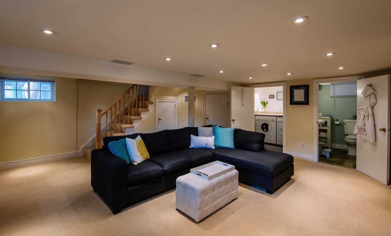A straight staircase leads to this basement with beige carpet flooring and a regular white ceiling fitted with recessed lights. It has a contrasting white tufted ottoman and black L-shaped sectional accented with blue pillows.
