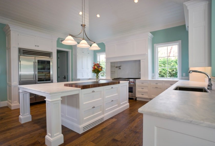 This is a Beach-style kitchen with gorgeous shiplap plank white ceiling blending with the bright white shaker cabinets and drawers of the kitchen island and the surrounding cabinetry lining the walls. These bright elements are complemented by the sea-green walls and hardwood flooring.