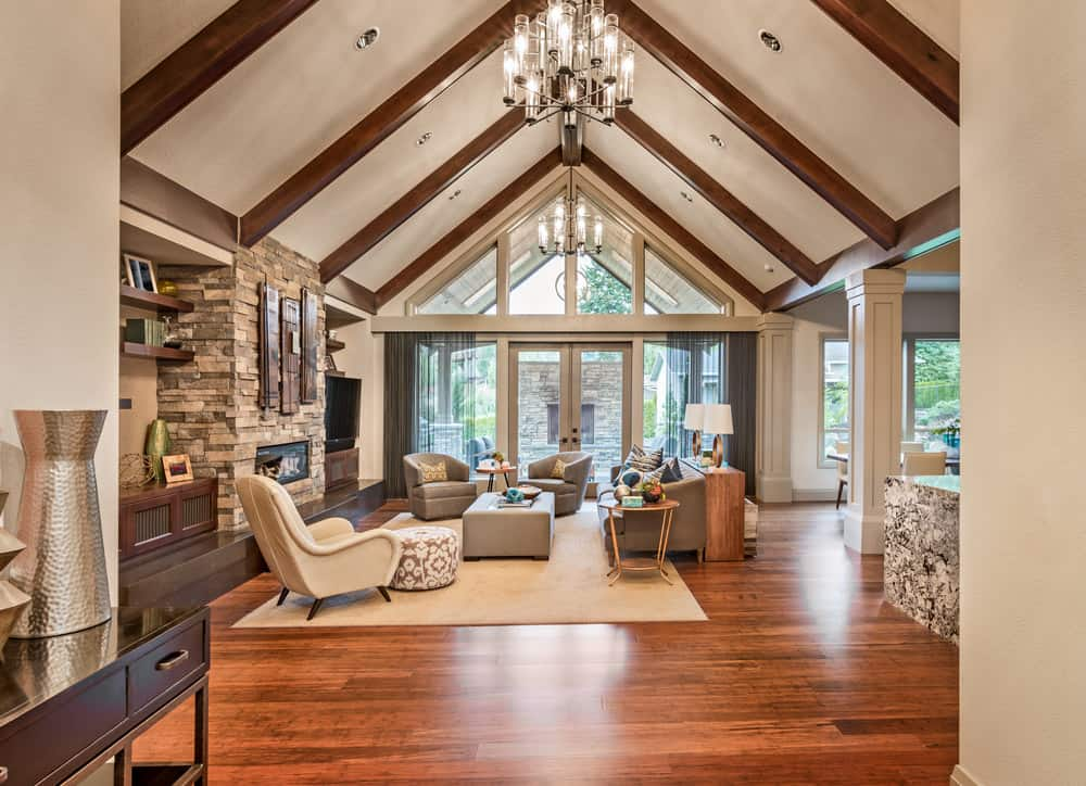 Spacious living room furnished with cozy upholstered seats and a gray ottoman that sits on a beige rug over the rich hardwood flooring. It is illuminated by a contemporary glass chandelier that hung from the cathedral ceiling lined with wood beams.