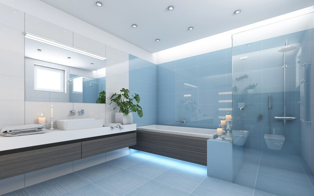 A modish blue master bathroom with blue tiles flooring and walls. The room offers a walk-in shower room, a drop-in deep soaking tub and a floating vanity with a large vessel sink.