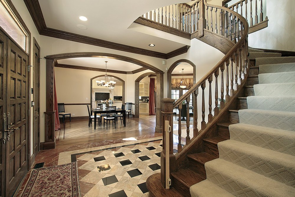 An entryway with gorgeous decorated tiles flooring. It also offers a curved staircase with carpeted steps.