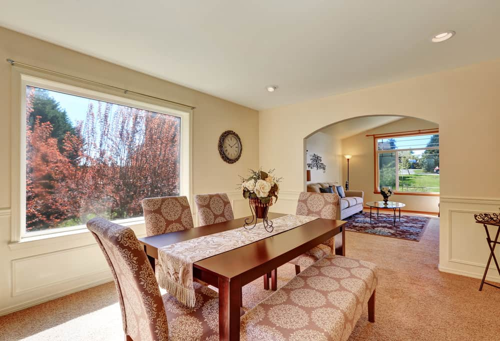 A tasseled runner lays on the smooth wooden table paired with a patterned bench and matching chairs. This dining room offers carpet flooring and beige wainscoted walls fitted with an open archway and a picture window.