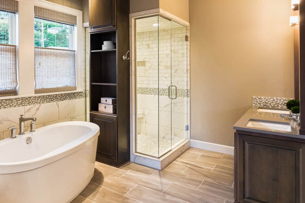Primary bathroom with beige walls and gorgeous flooring. It has a sink counter with two sinks and a walk-in corner shower room. There's a large freestanding tub as well.