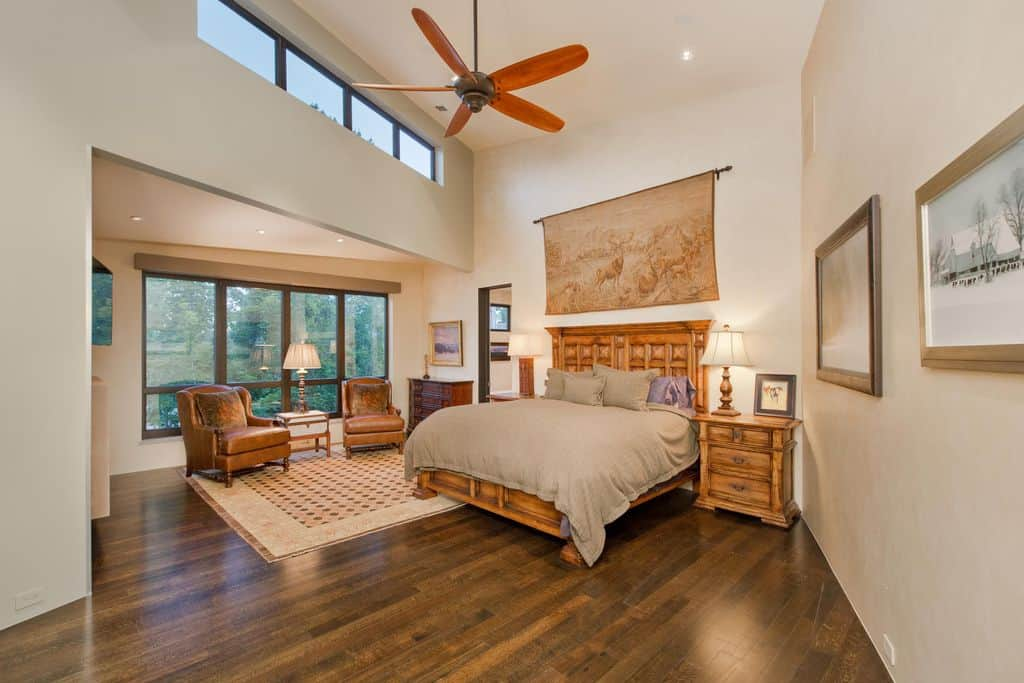 This primary bedroom features a sitting area by the glass paneled windows along with a cozy wooden bed highlighted by a woodland tapestry. It has beige walls and a high ceiling mounted with a bronze fan and recessed lights.