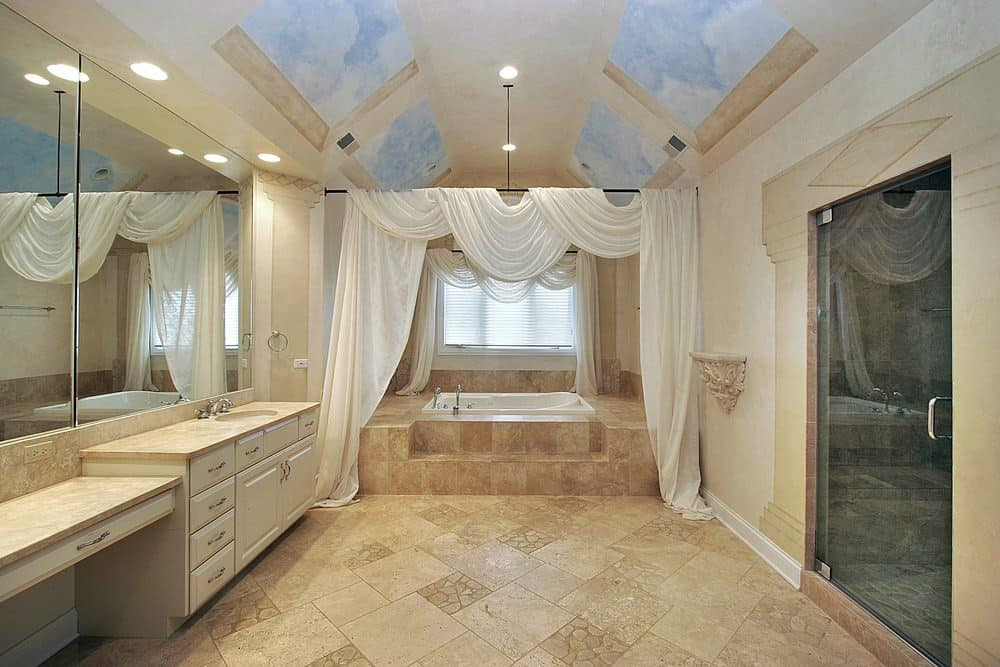 This Mediterranean primary bathroom boasts beige tiles flooring and walls, along with a beautiful custom ceiling. The room offers a drop-in tub along with a large walk-in shower room.