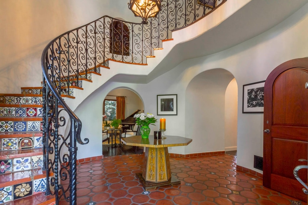 Upon entry of the house, you are welcomed by this foyer that has terracotta flooring tiles to contrast the beige walls. You can see in the middle that there is a wooden table with decors on top.