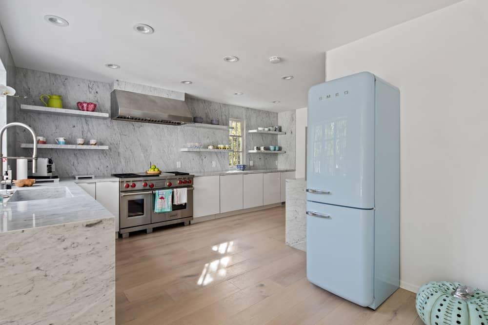 L-shaped kitchen featuring a stunning marble kitchen countertop matching the backsplash walls.