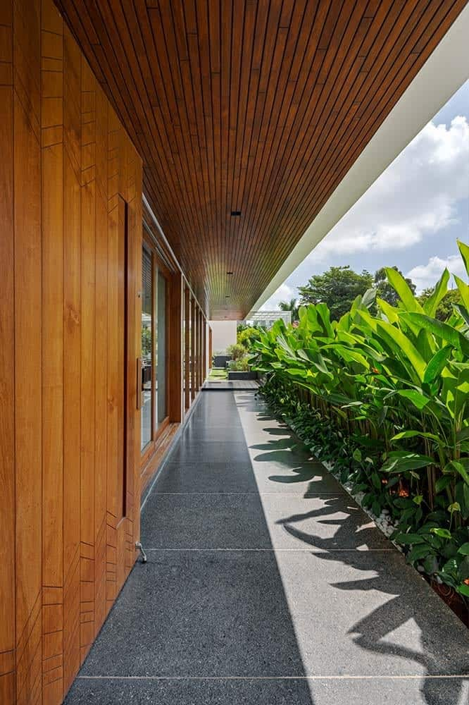 This is a close look at the front of the house with a walkway of gray tiles topped with a wooden ceiling. These are then complemented by the row of tropical plants on the side across from the glass walls.