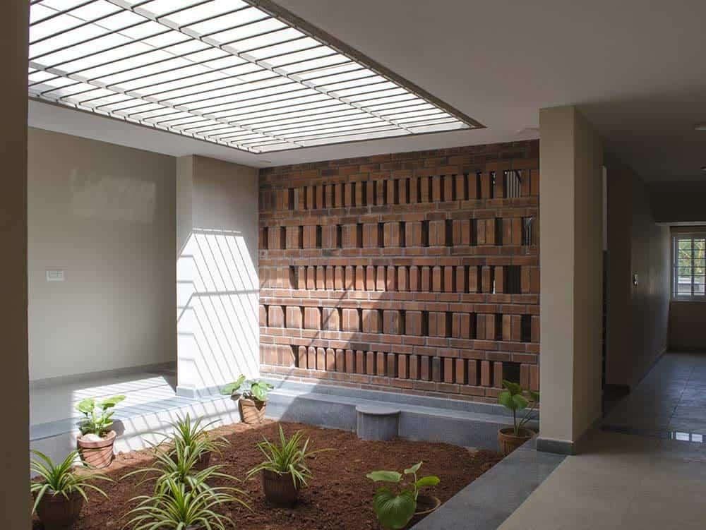 This is a close look at the indoor Zen garden of the house with a few potted plants, red brick wall and a skylight above it.