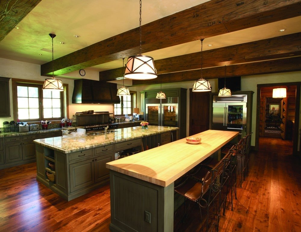 The kitchen has enough space for two kitchen islands on its hardwood flooring. These have a dark gray tone to its wooden body contrasted by the bright beige countertop that match the ceiling.