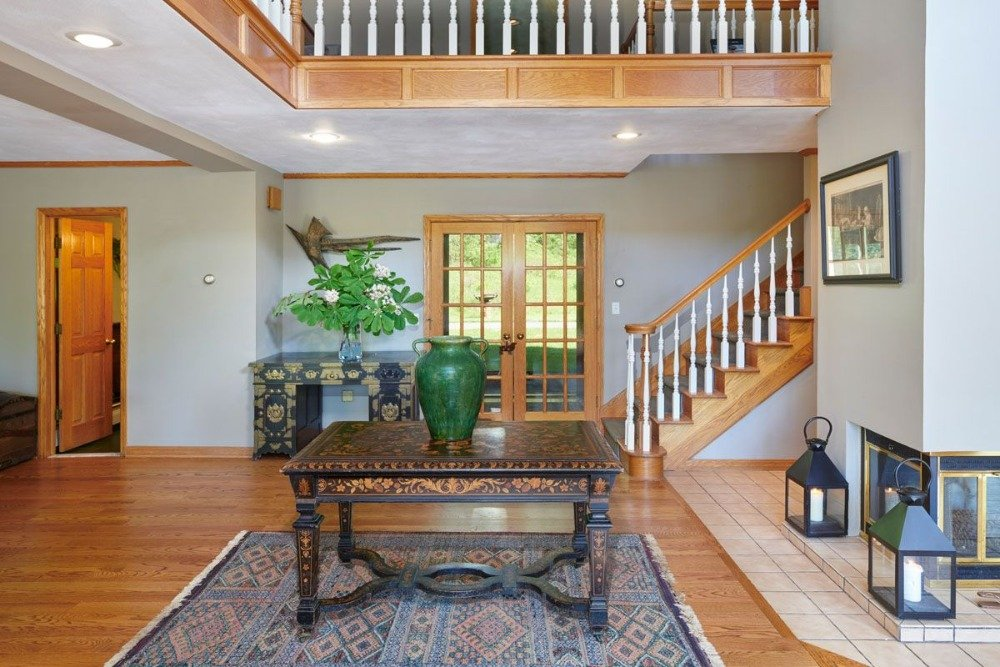 Entry of the house with an elegant centerpiece table on top of an area rug.