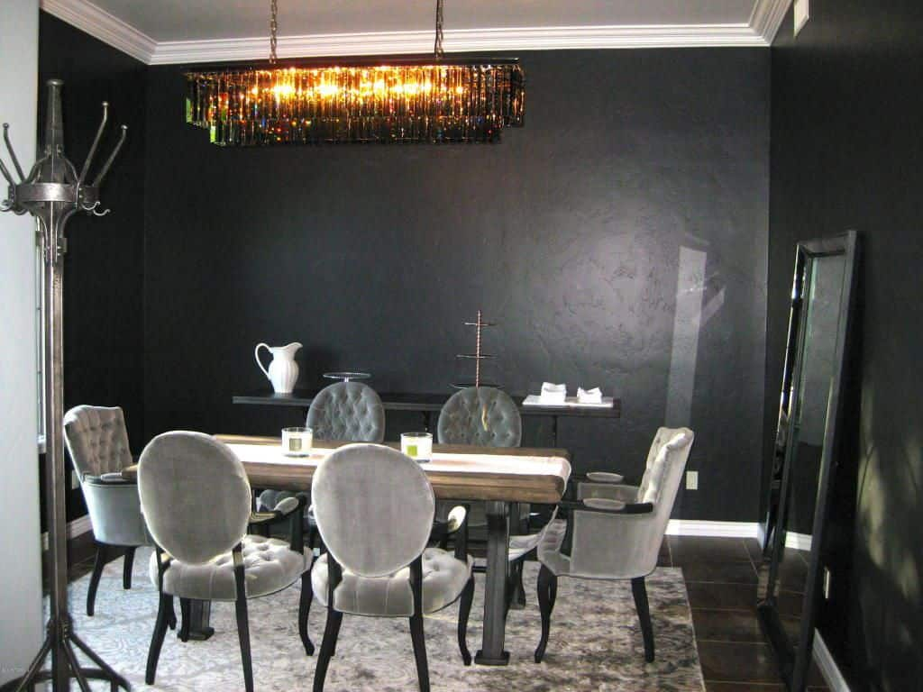 Black dining room decorated with a full-length mirror and an eccentric cascading chandelier hanging over the wooden dining table that's lined with a white runner. It is surrounded by gray tufted chairs that sit on a matching area rug over tiled flooring.