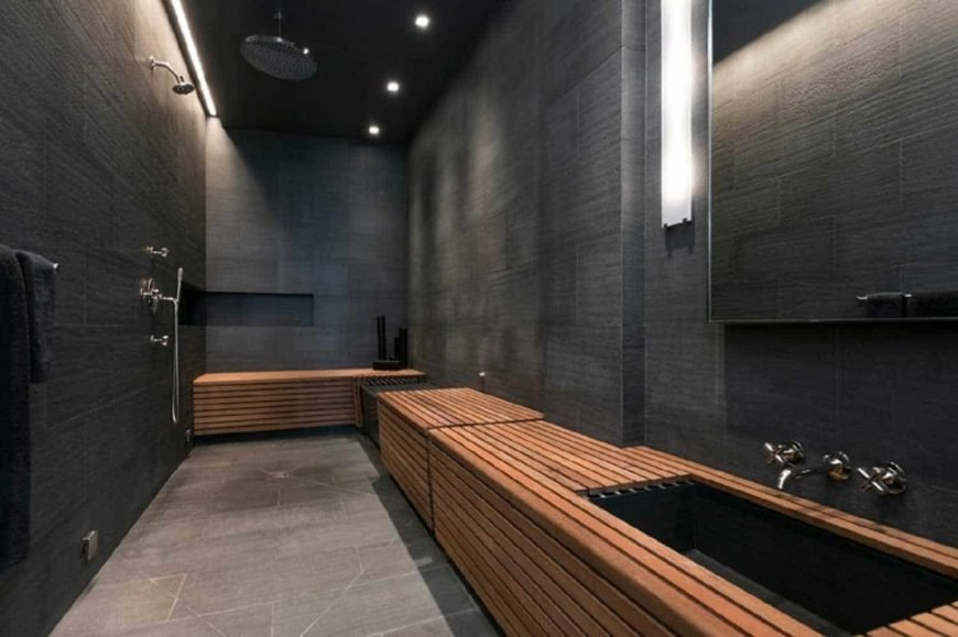 Modern master bathroom featuring black walls and a black ceiling. It offers stylish sink counter and open showers.