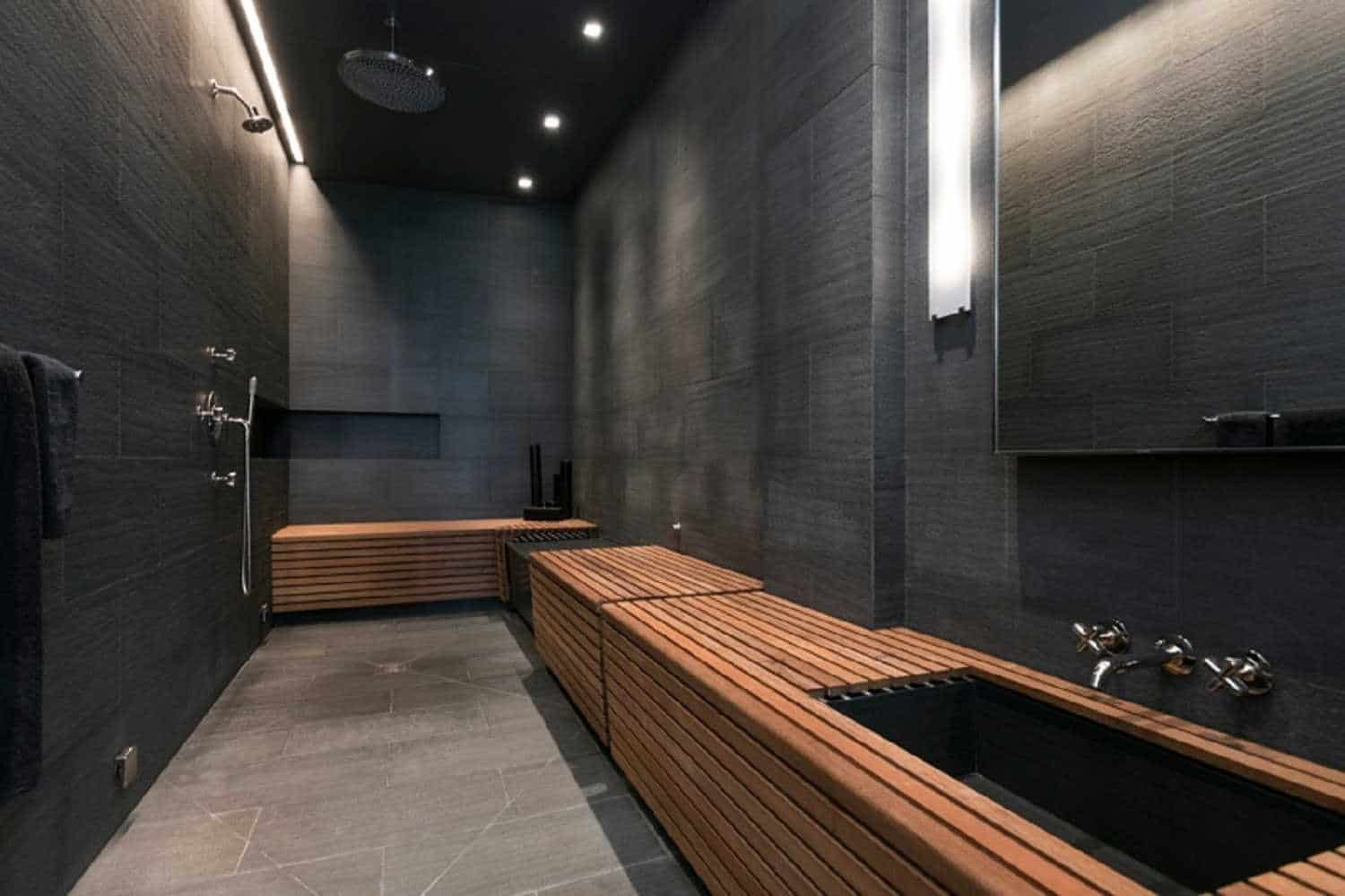 Modern primary bathroom featuring black walls and a black ceiling. It offers stylish sink counter and open showers.