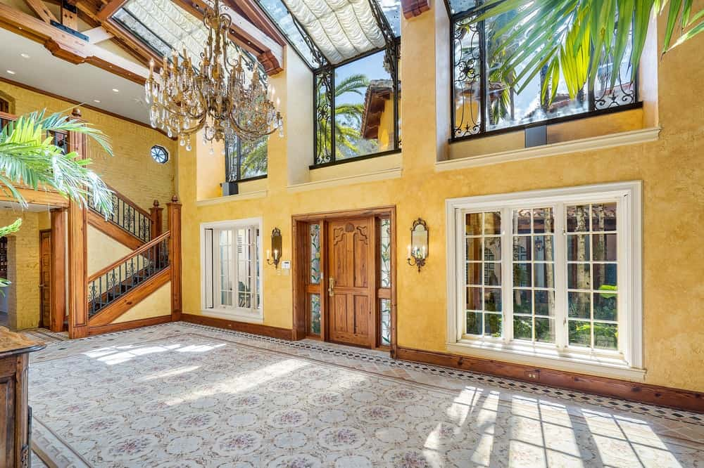 Spacious entry foyer with carpeted flooring, a tall ceiling, yellow walls and a glamorous grand chandelier.