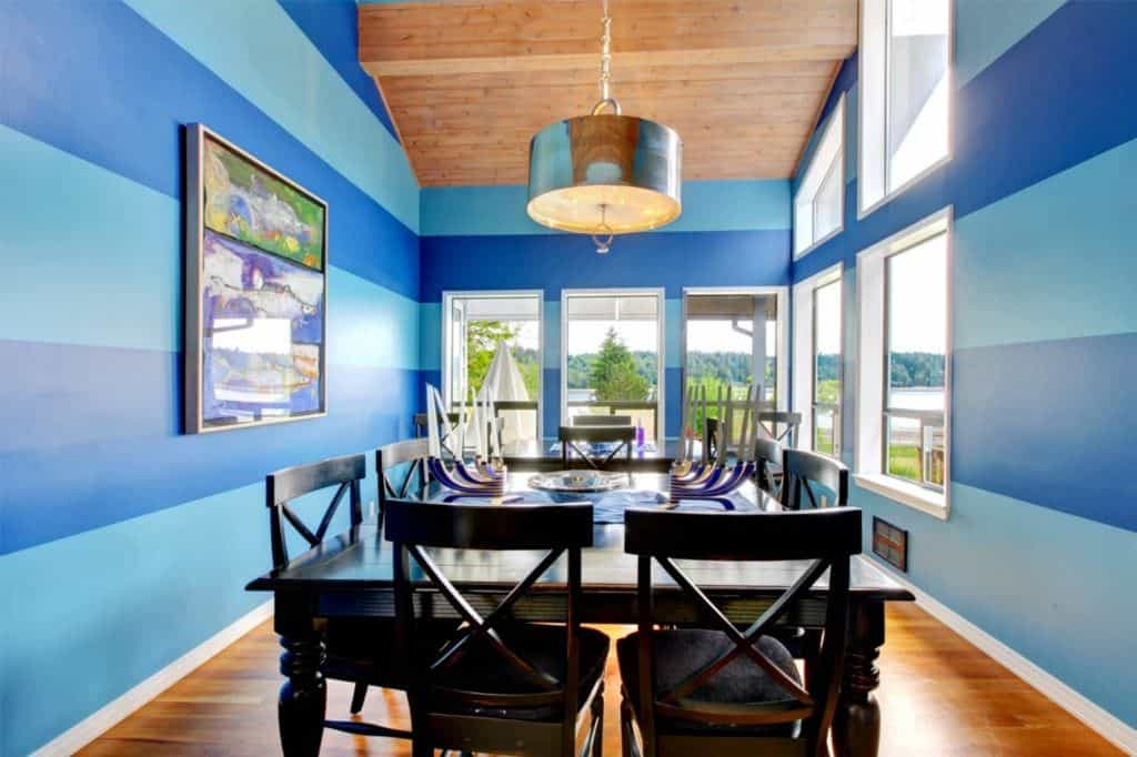 Airy dining room with a serene outdoor view boasting a dark wood dining set lighted by a chrome drum chandelier that hung from the wood plank ceiling. It is decorated with a gorgeous artwork mounted on the blue striped wallpaper.