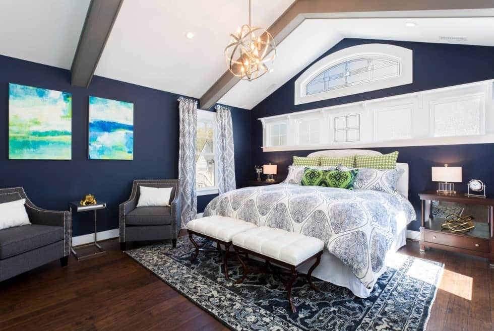 A spherical chandelier that hung from the cathedral ceiling illuminates this primary bedroom offering a sitting area and a comfy bed that sits on a classic area rug over the wide plank flooring. It is surrounded by deep blue walls mounted with abstract paintings.